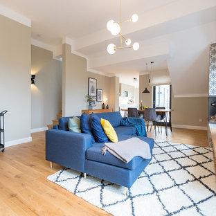 Offenes, Großes Modernes Wohnzimmer mit Eckkamin, gefliester Kaminumrandung, Wand-TV, braunem Boden, beiger Wandfarbe und braunem Holzboden in Berlin