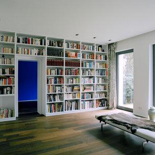 Modelo de biblioteca en casa abierta, moderna, grande, con paredes blancas y suelo de madera en tonos medios