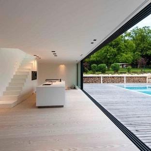 Geräumiges, Offenes Modernes Wohnzimmer mit weißer Wandfarbe und hellem Holzboden in Sonstige