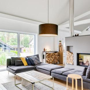 Großes, Repräsentatives, Offenes Modernes Wohnzimmer mit weißer Wandfarbe, Porzellan-Bodenfliesen, Kamin, verputzter Kaminumrandung, braunem Boden und freigelegten Dachbalken in Berlin