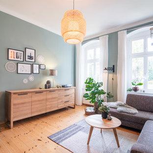 Großes Nordisches Wohnzimmer mit grüner Wandfarbe, braunem Holzboden und braunem Boden in Berlin