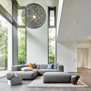 Großes, Fernseherloses Modernes Wohnzimmer im Loft-Style mit weißer Wandfarbe, braunem Holzboden und grauem Boden in Sonstige