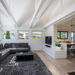 Großes, Abgetrenntes Modernes Wohnzimmer mit weißer Wandfarbe, hellem Holzboden, Kamin, Kaminsims aus Stein, Wand-TV und braunem Boden in Stuttgart