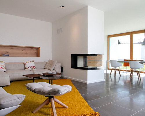 Großes, Offenes Modernes Wohnzimmer Mit Weißer Wandfarbe, Verputztem  Kaminsims, Marmorboden Und Kaminofen In