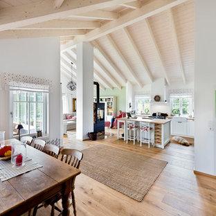 Großes, Offenes Landhaus Wohnzimmer Mit Weißer Wandfarbe, Hellem Holzboden,  Kaminofen, Kaminsims Aus