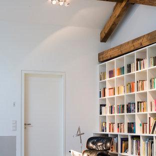 Mittelgroße, Fernseherlose, Abgetrennte Moderne Bibliothek ohne Kamin mit weißer Wandfarbe, Betonboden und grauem Boden in Köln