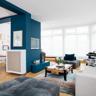 Repräsentatives, Offenes, Großes Modernes Wohnzimmer ohne Kamin mit blauer Wandfarbe, hellem Holzboden, Wand-TV und beigem Boden in Berlin