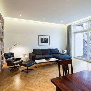 デュッセルドルフの中サイズのコンテンポラリースタイルのおしゃれなファミリールーム (ライブラリー、白い壁、無垢フローリング、暖炉なし、茶色い床) の写真