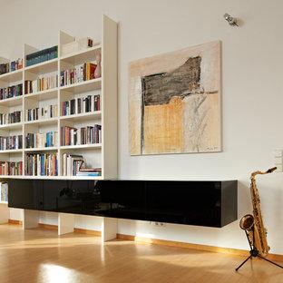 Mittelgroßes, Fernseherloses, Abgetrenntes Modernes Musikzimmer ohne Kamin mit weißer Wandfarbe, braunem Holzboden und braunem Boden in Stuttgart