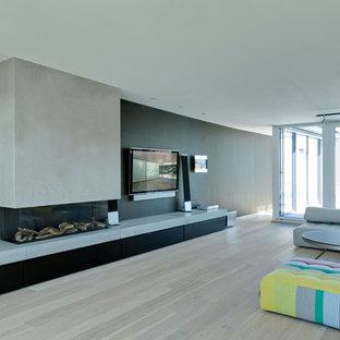 Idée de décoration pour une salle de séjour design ouverte avec un mur noir, un sol en bois clair, une cheminée ribbon, un manteau de cheminée en béton et un téléviseur fixé au mur.