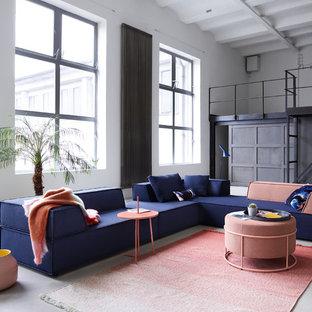 Geräumiges, Fernseherloses Industrial Wohnzimmer ohne Kamin, im Loft-Stil mit weißer Wandfarbe, Betonboden und grauem Boden in Stuttgart