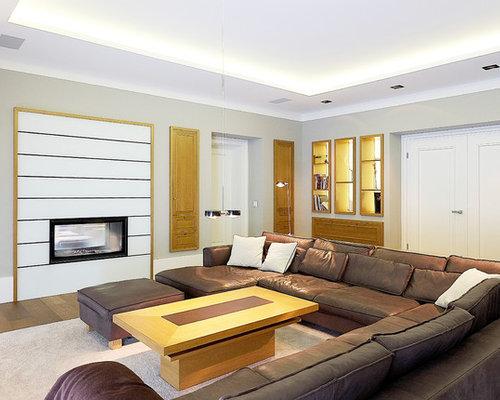 Geräumiges, Abgetrenntes Modernes Wohnzimmer Mit Grauer Wandfarbe,  Tunnelkamin, Braunem Holzboden, Kaminsims Aus
