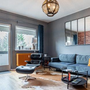 Industrial Wohnzimmer mit grauer Wandfarbe, braunem Holzboden und braunem Boden in Berlin