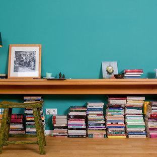 Imagen de salón contemporáneo con paredes azules, suelo de madera clara y suelo marrón