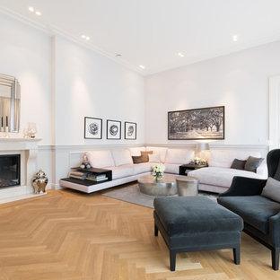 Repräsentatives, Fernseherloses Klassisches Wohnzimmer mit weißer Wandfarbe, braunem Holzboden, Kamin und braunem Boden in Köln