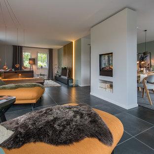 Offenes, Geräumiges, Repräsentatives Modernes Wohnzimmer mit weißer Wandfarbe, Tunnelkamin, verputzter Kaminumrandung, schwarzem Boden und freistehendem TV in Hamburg