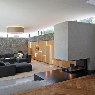 ミュンヘンの大きいコンテンポラリースタイルのおしゃれなファミリールーム (グレーの壁、コンクリートの床、コンクリートの暖炉まわり、内蔵型テレビ、グレーの床、両方向型暖炉) の写真