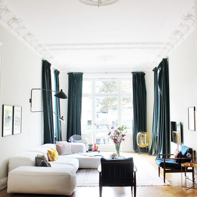 Mid-sized eclectic enclosed medium tone wood floor and brown floor family room photo in Hamburg with white walls