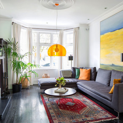 Example of a mid-sized eclectic dark wood floor and brown floor family room design in London with white walls, a wood stove and no tv