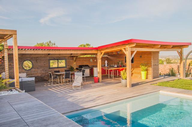 Réalisation d'un grand jardin avec une terrasse en bois ou composite arrière design l'été avec un mur de soutènement et une exposition ensoleillée.