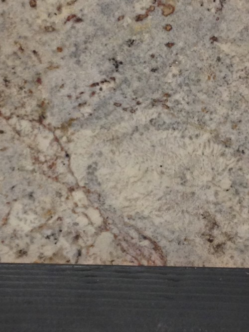 Spring White Leathered Granite With Ceasarstone Raven