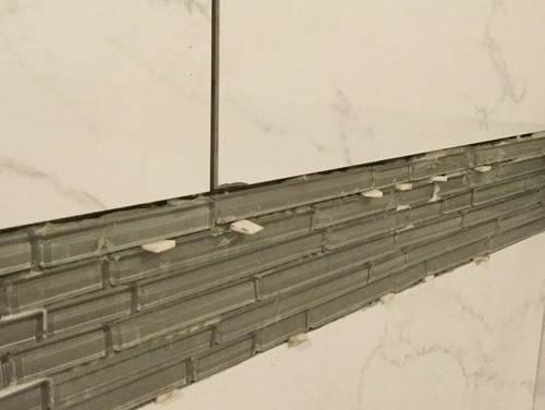 Chipped porcelain tile in shower? Contractor at fault?