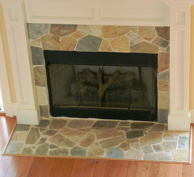 Neutral natural stone fireplace with white mantel.
