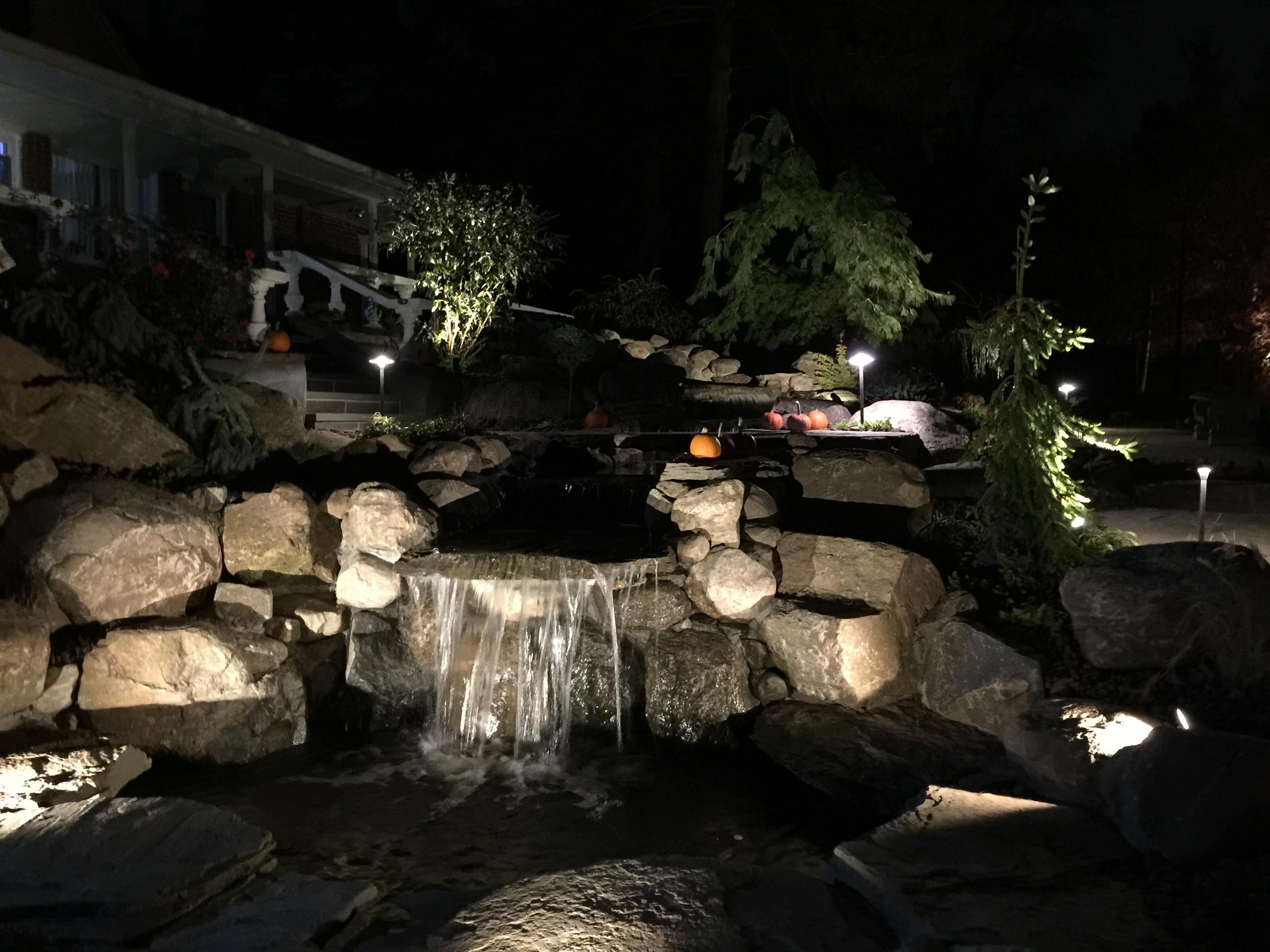 waterfall stream with stone bridge and natural bluestone walkwayway and steps