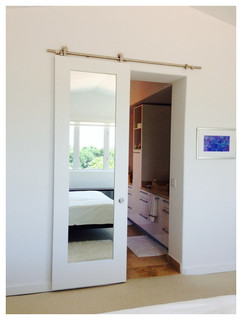 White Primed Mirror Doors On A Sliding Barn Door Track