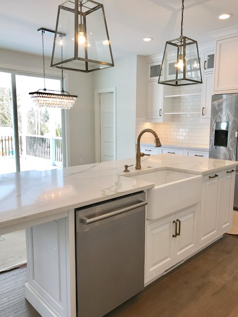 Kitchen - large country medium tone wood floor and brown floor kitchen idea in Cleveland with a farmhouse sink, raised-panel cabinets, white cabinets, quartzite countertops, white backsplash, subway tile backsplash, stainless steel appliances and an island