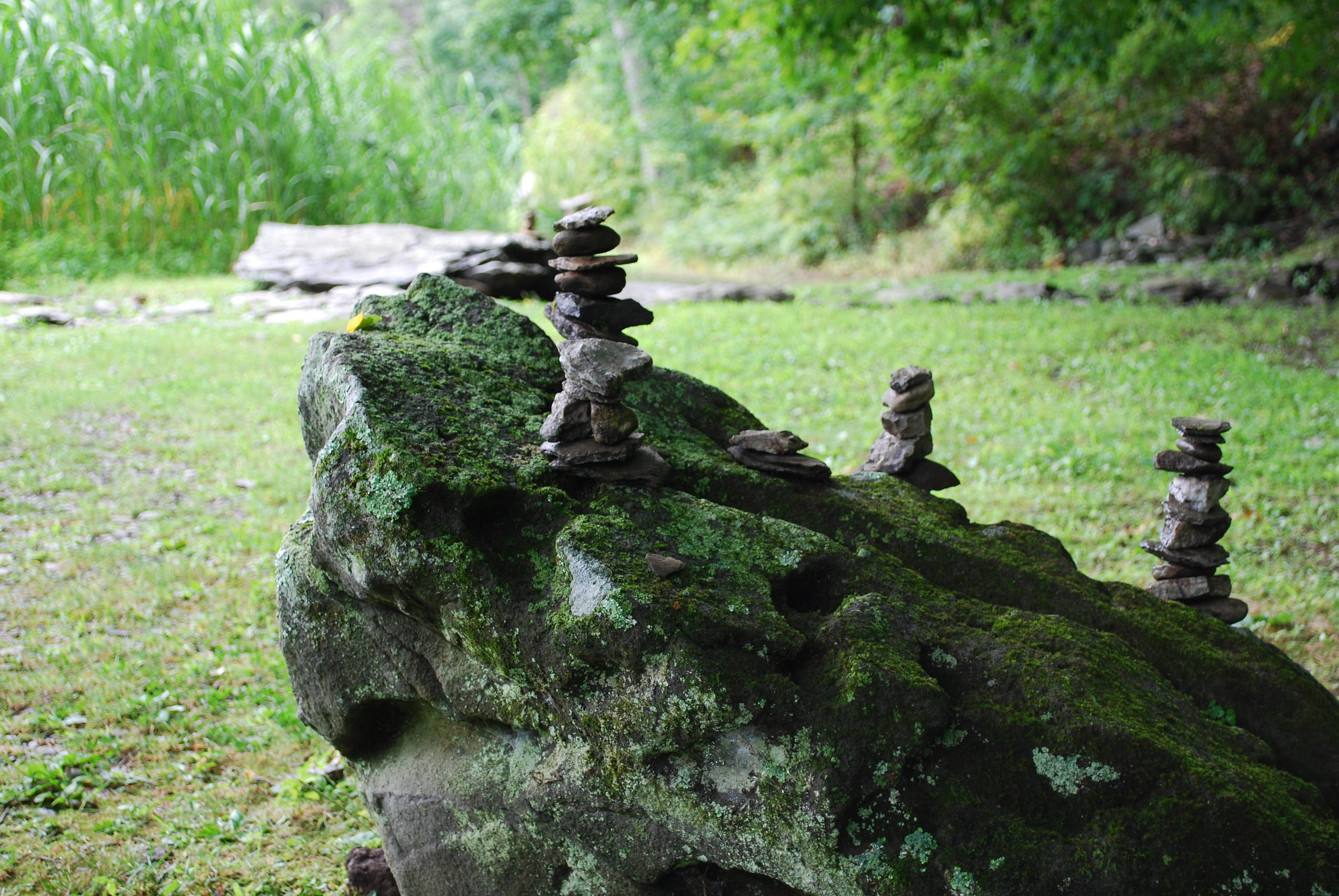 Meditative stone stacking on boulder.