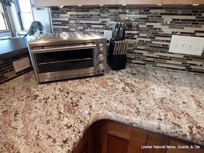 here is your granite with a mosaic backsplash different colors than yours but it kind of gives an idea of patterns
