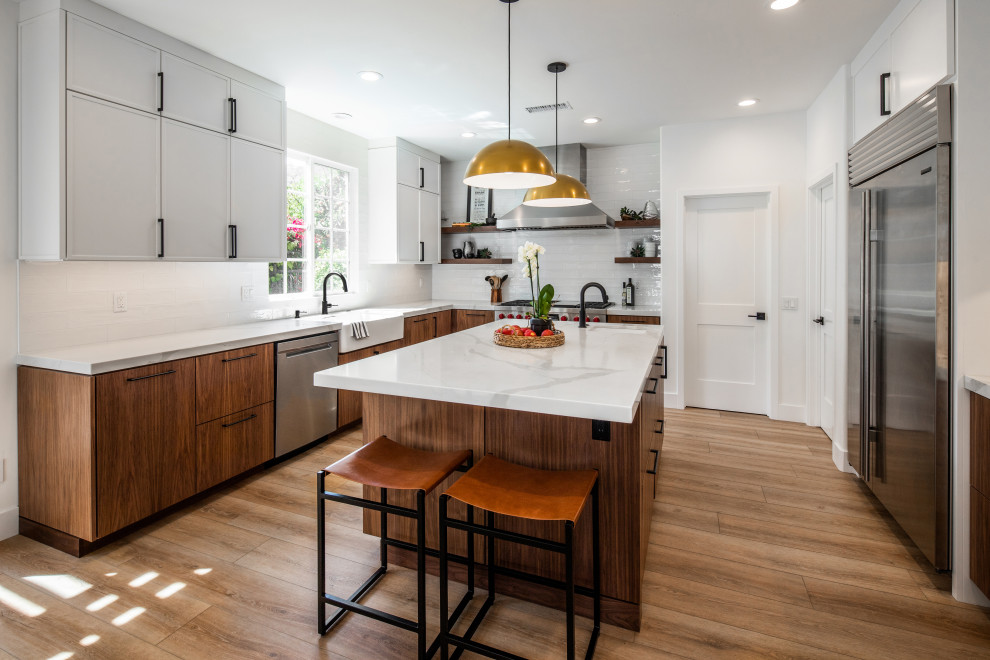 Example of a mid-sized 1950s u-shaped laminate floor and beige floor open concept kitchen design in San Diego with a farmhouse sink, flat-panel cabinets, medium tone wood cabinets, marble countertops, white backsplash, ceramic backsplash, stainless steel appliances, an island and white countertops