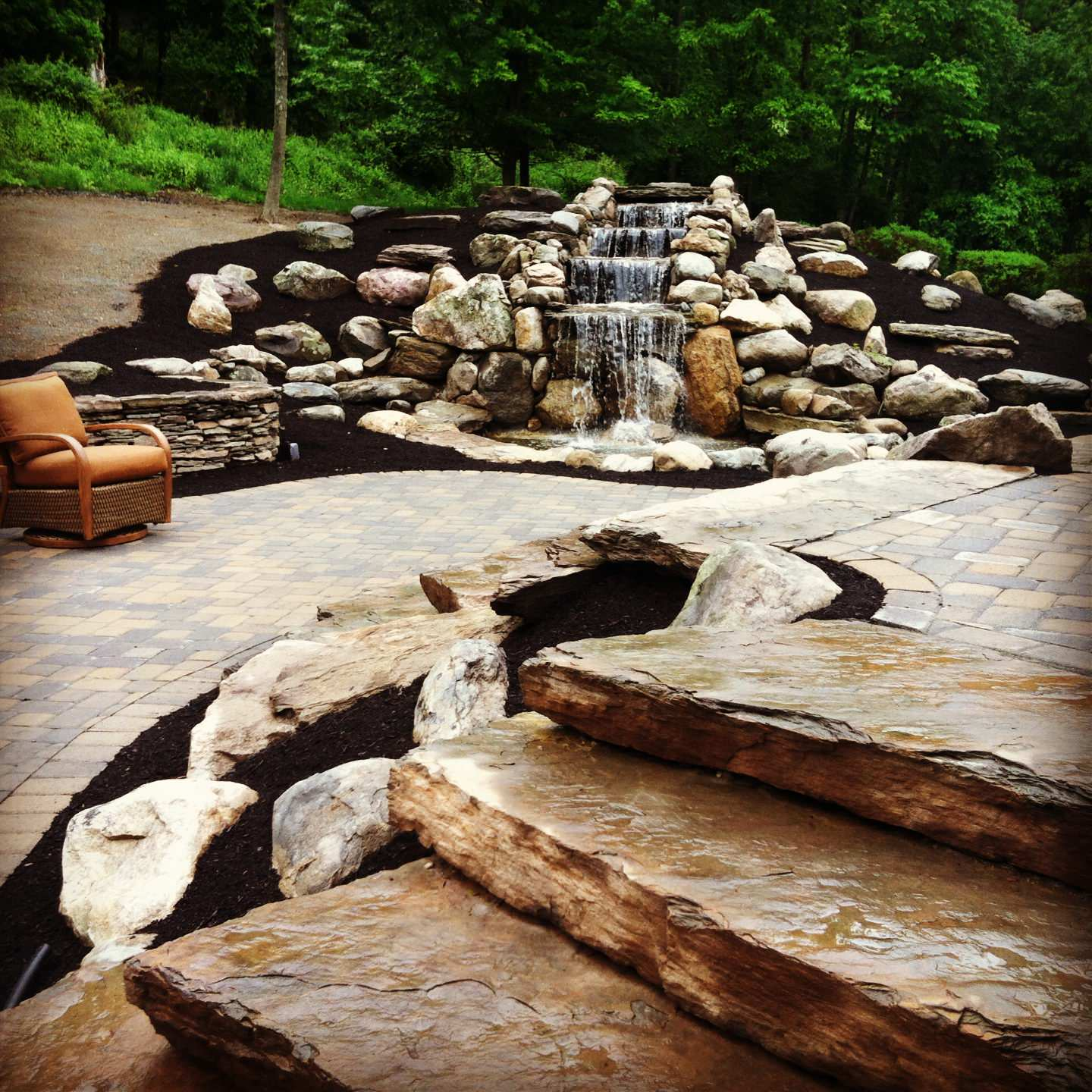 waterfall natural fieldstone walls with two tiered paver patio