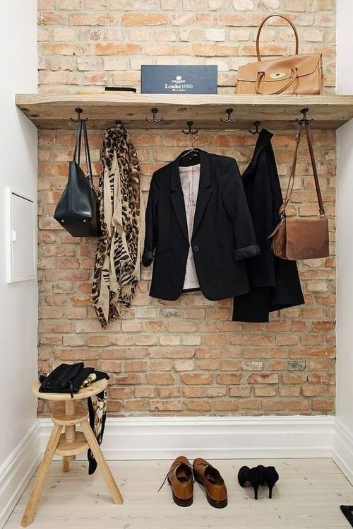 Un recibidor muy pequeño con estilo industrial rústico y pared de ladrillo