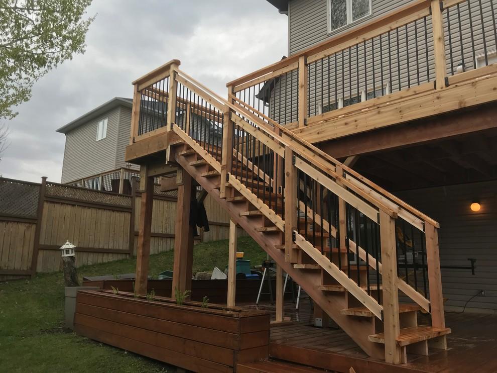Walk-out red cedar deck with black round spindles, custom cut 2 x 12 cedar strin