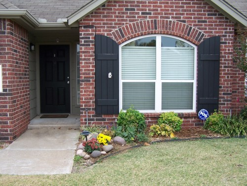 My Small House Has A Black Front Door And Two Shutters On One Of The Front Windows The Brick