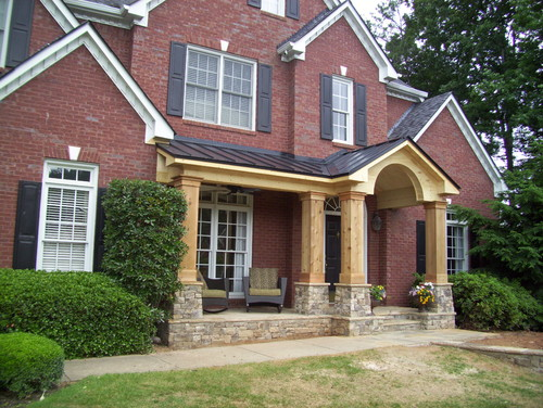 Unpainted front porch addition to traditional brick home for Georgia front porch