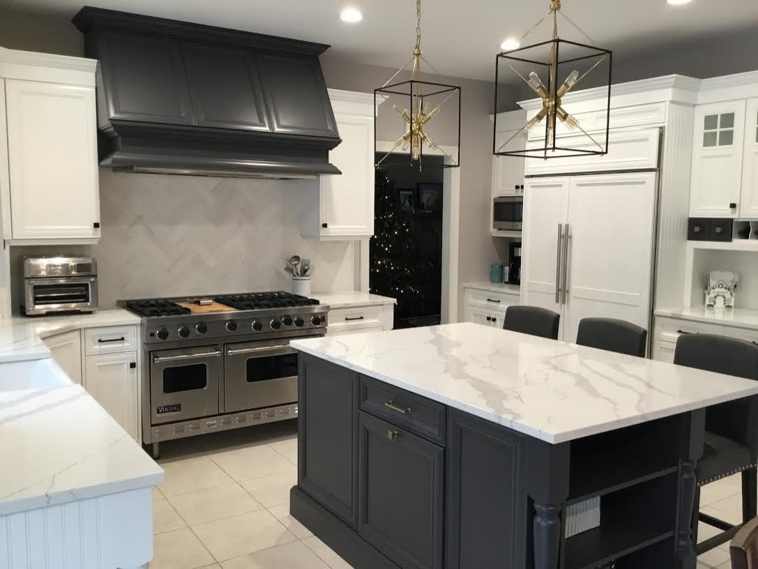 A Transitional Kitchen with a gorgeous Herringbone marble backsplash