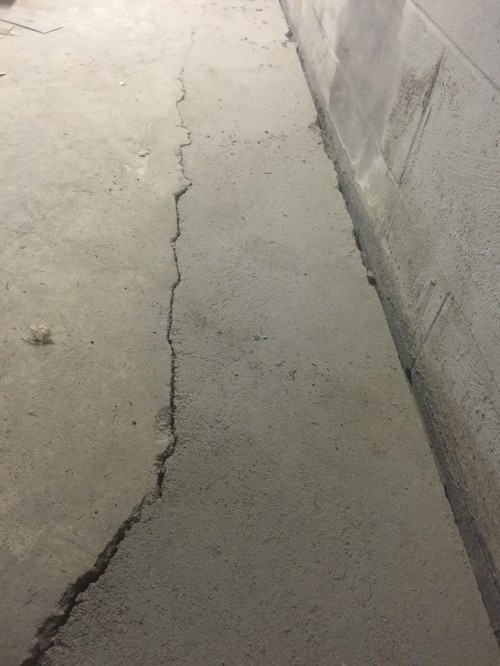 Basement concrete floor heaving cracking at french drain for Crumbling concrete floor