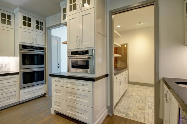 Enclosed kitchen - large contemporary l-shaped medium tone wood floor enclosed kitchen idea in Other with an undermount sink, beaded inset cabinets, white cabinets, granite countertops, white backsplash, stone slab backsplash, stainless steel appliances and an island