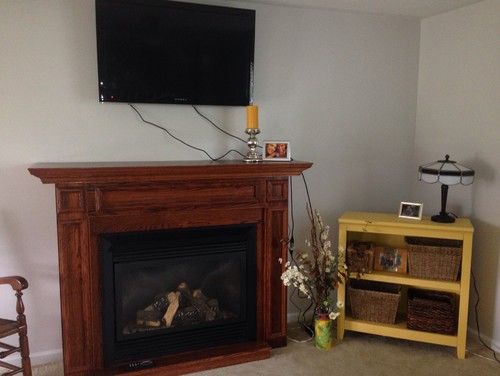 mounted tv above gas fireplace now how to hide these hideous cords from it..