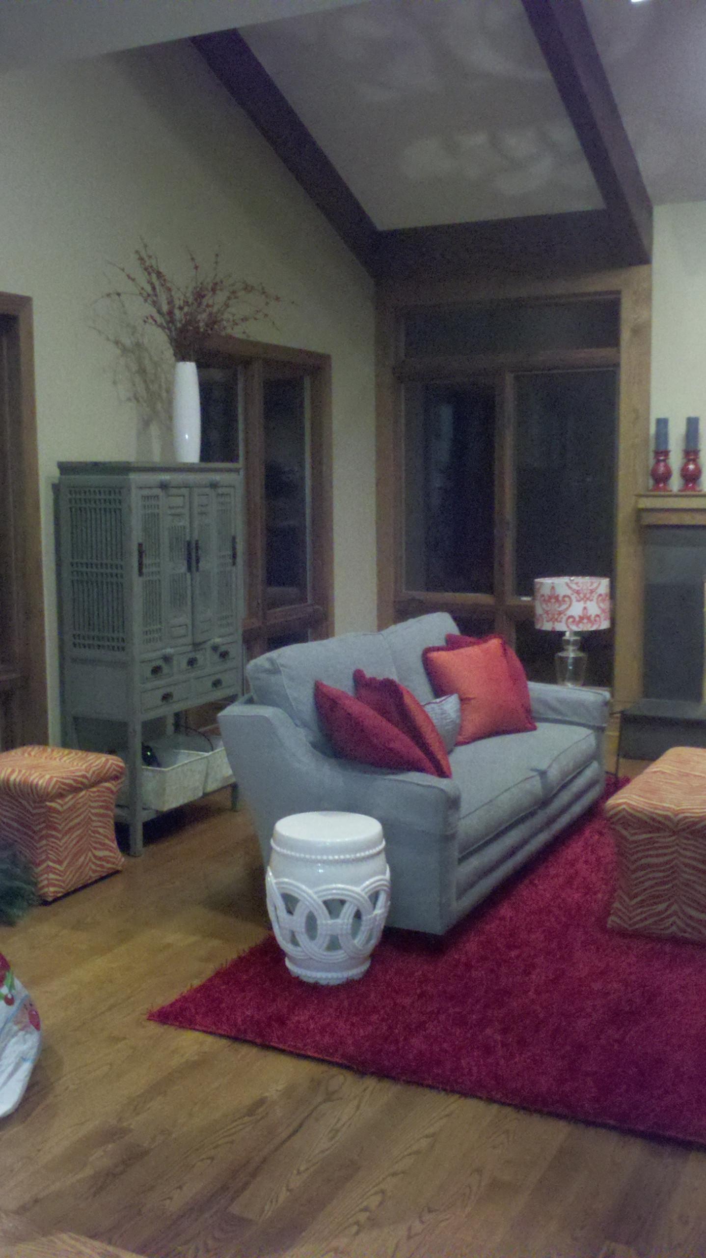 living room based on red, orange, blue paisley print, red shag rug, antiques