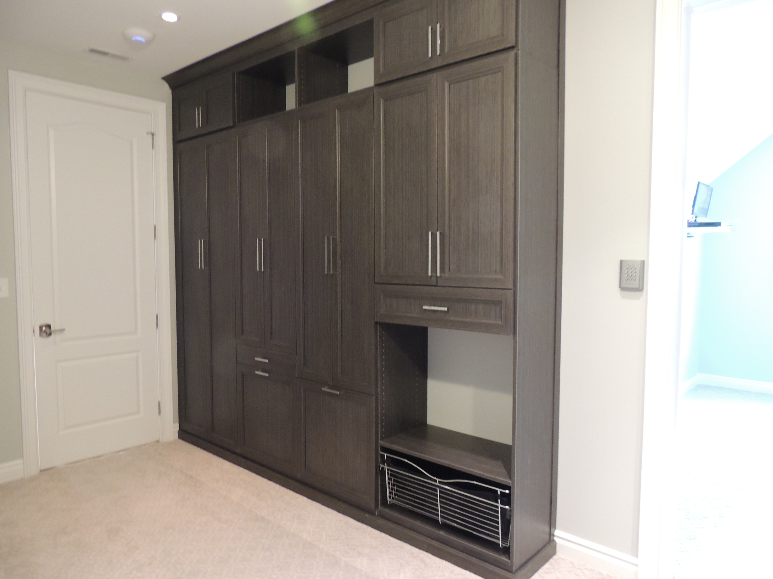 Shaker door cabinets for hamper and ironing board storage.