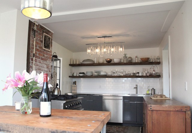 Example of a mountain style kitchen design in Vancouver with stainless steel appliances, subway tile backsplash, open cabinets, black cabinets, white backsplash and stainless steel countertops