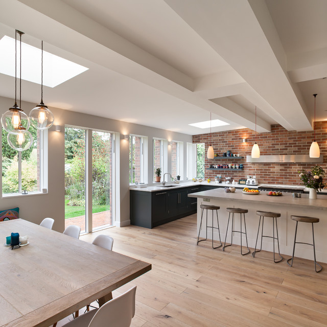 Design ideas for a large contemporary l-shaped kitchen/diner in London with a built-in sink, flat-panel cabinets, grey cabinets, concrete worktops, integrated appliances, medium hardwood flooring and a breakfast bar.
