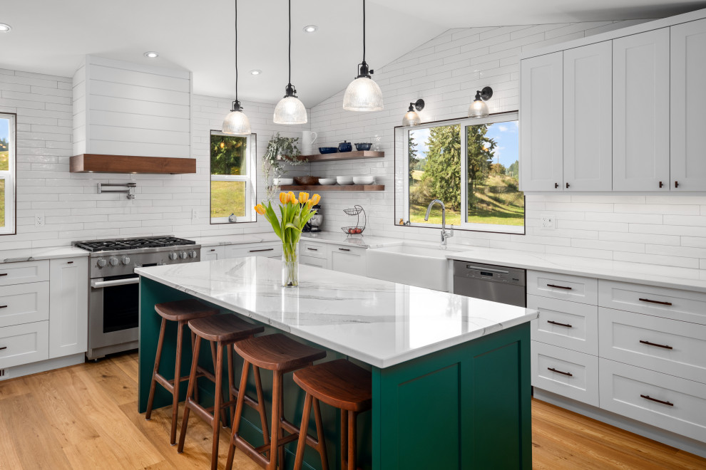 Inspiration for a farmhouse u-shaped laminate floor and beige floor kitchen remodel in Vancouver with a farmhouse sink, white cabinets, white backsplash, porcelain backsplash, stainless steel appliances, an island and white countertops