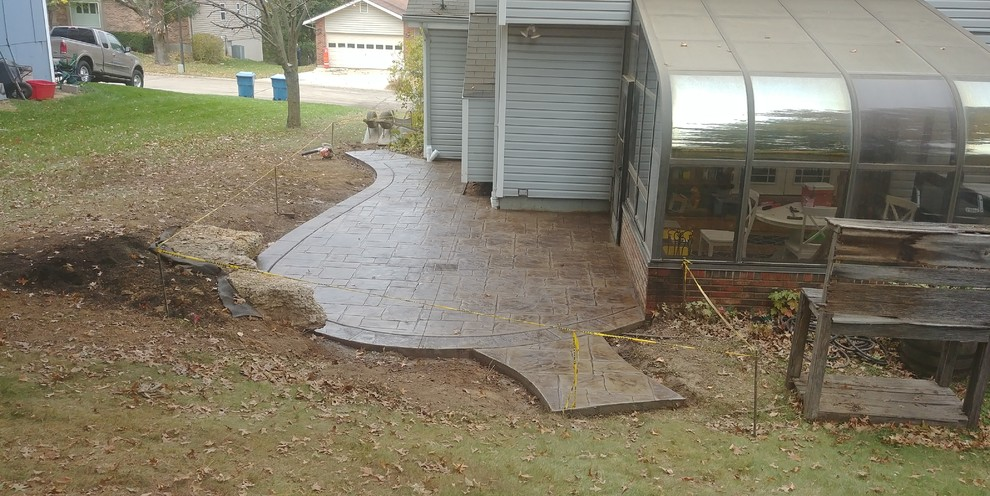 Stamped Concrete Patio with limestone boulder sitting wall in St Charles Missou