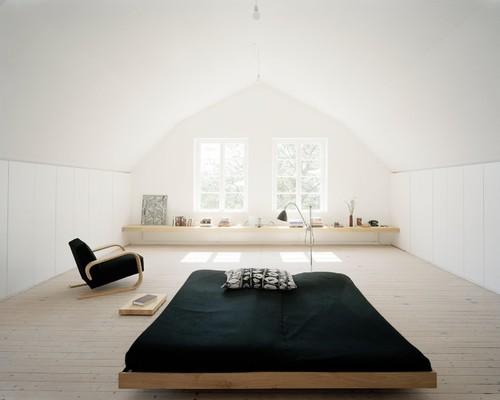 Attic bedroom in black and light wood tones at Råman House