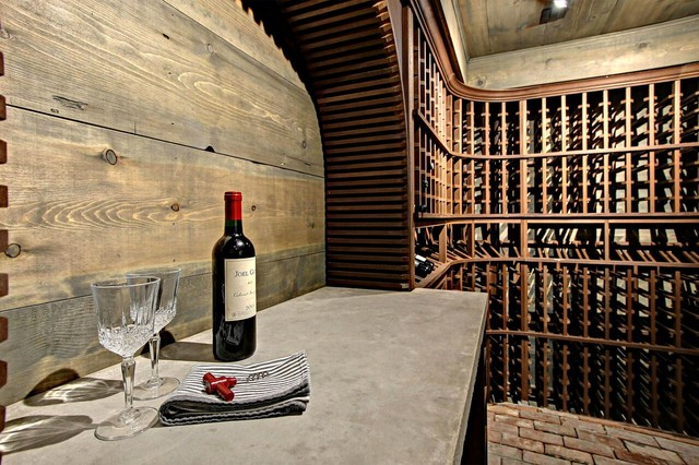 Example of a transitional brick floor wine cellar design in Other with display racks